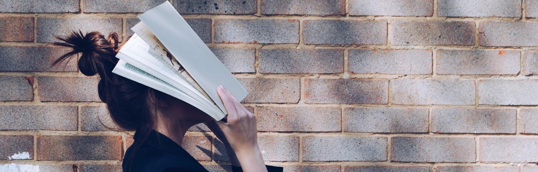 nainen kurkistaa kirjan takaa