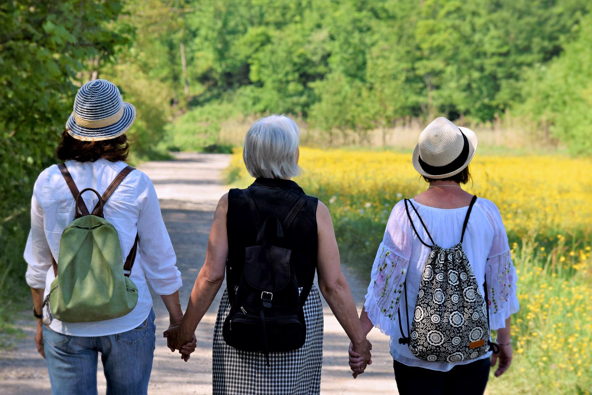 kolme naista kävelee luonnossa käsikkäin