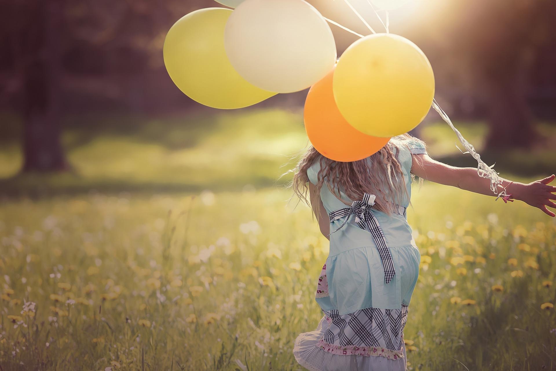 lapsi juoksee ilmapallojen kanssa