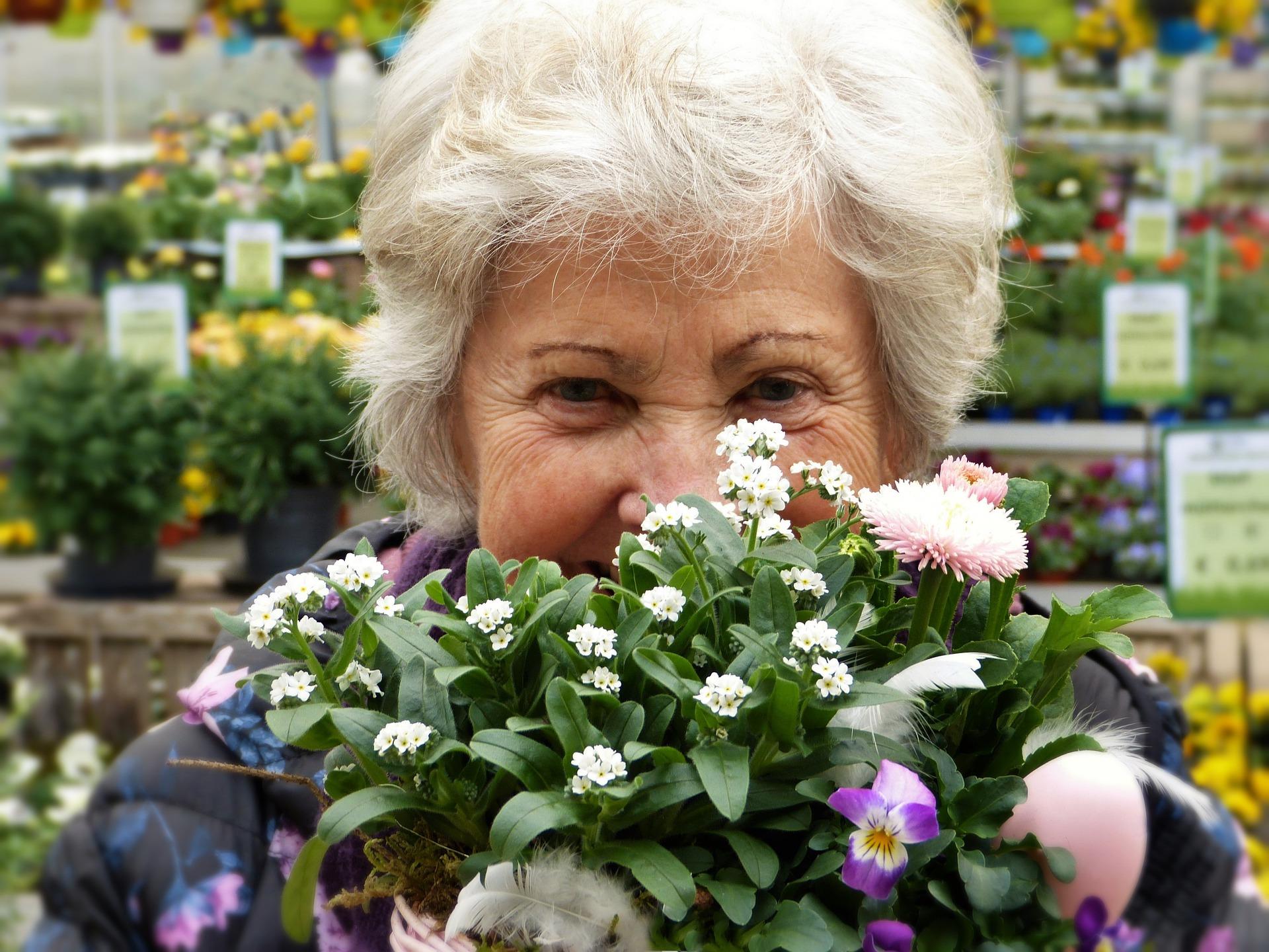 iäkäs nainen haistelee kukkia
