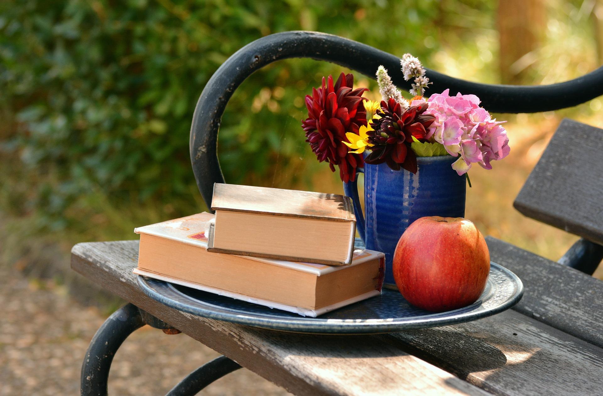kirjoja ja kukkia penkillä